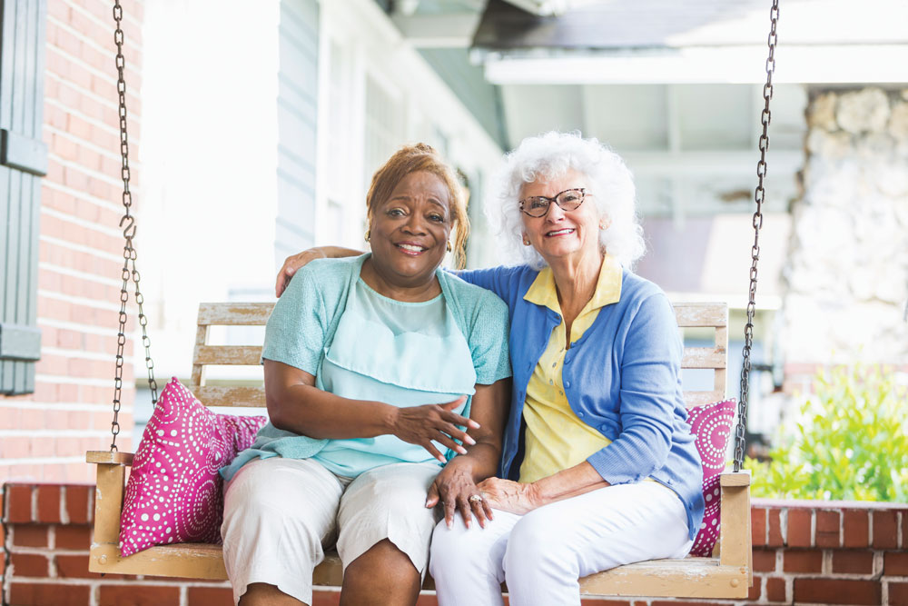 Assisted Living residents sitting on porch swing enjoying the lifestyle at the cottages