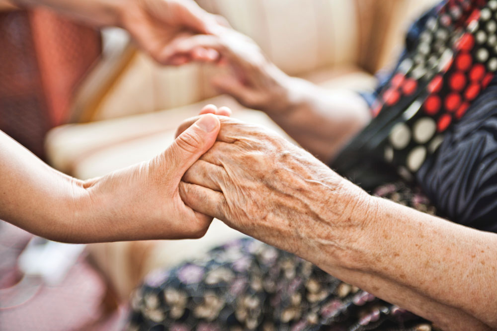 Cottages of Fox Lake - Memory care senior living resident grasping hands with young adult