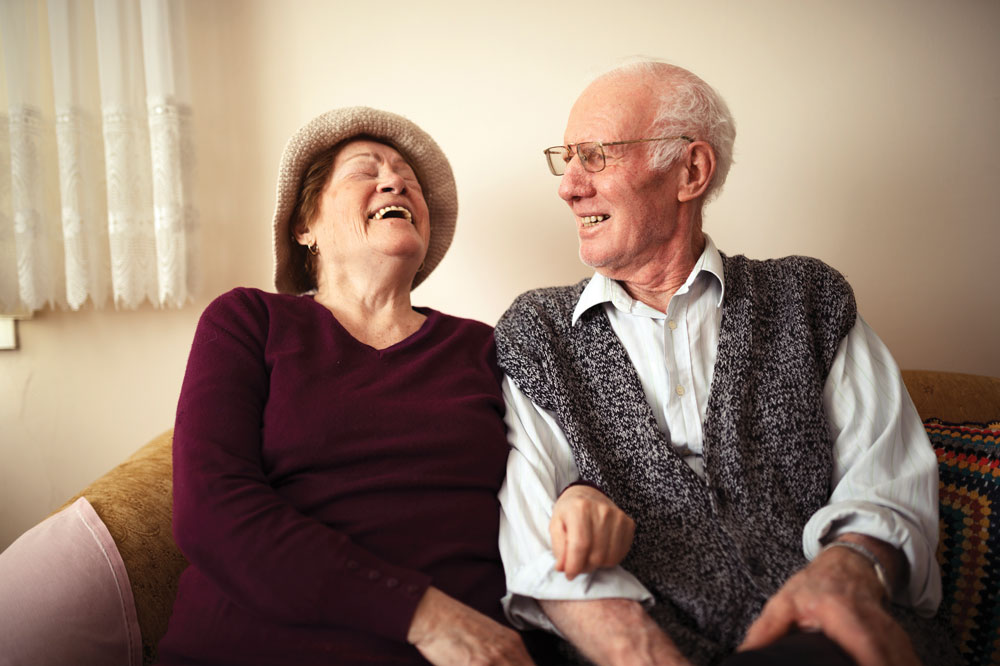 Two The Cottage of Fox Lake memory care residents sitting beside each other on couch and laughing